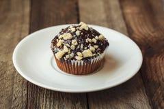 Muffin dolce delizioso sveglio con cioccolato su fondo di legno Fotografia Stock