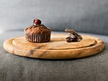 Muffin and eaten muffin on wooden plate royalty free stock photography