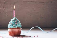 Muffin eller en liten kaka med en brinnande stearinljus begrepp av lyckönskan, ferie Arkivbild