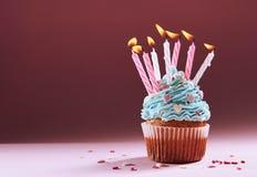 Muffin eller en liten kaka med en brinnande stearinljus begrepp av lyckönskan, ferie Royaltyfria Bilder
