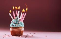 Muffin eller en liten kaka med en brinnande stearinljus begrepp av lyckönskan, ferie Arkivbilder