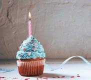 Muffin eller en liten kaka med en brinnande stearinljus begrepp av lyckönskan, ferie Royaltyfri Bild