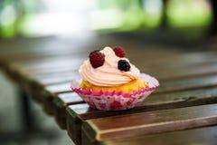 Muffin eller muffin med kräm med lösa bär royaltyfri foto