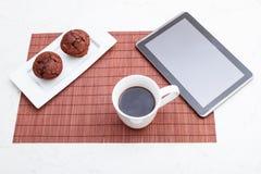 Muffin för chokladchiper med en kopp kaffe och en minnestavlaPC Fotografering för Bildbyråer