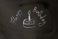 Muffin för lycklig födelsedag för kritainskrift med stearinljuset Arkivfoton