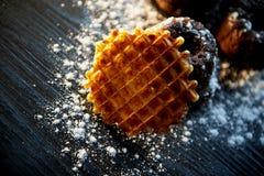 Muffin freschi fertili del cioccolato spruzzati con zucchero in polvere, disposizione contro il legno scuro Cialde belghe rotonde Fotografia Stock