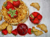 Muffin and fresh strawberries, croissants , cake with almonds Royalty Free Stock Photos
