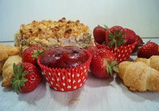 Muffin and fresh strawberries, croissants , cake with almonds Stock Photo