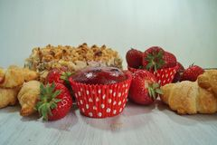 Muffin and fresh strawberries, croissants , cake with almonds Stock Image