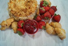 Muffin and fresh strawberries, croissants , cake with almonds Royalty Free Stock Photography