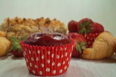 Muffin and fresh strawberries, croissants , cake with almonds Royalty Free Stock Photo
