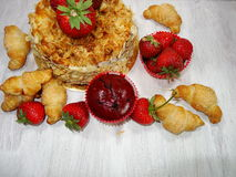 Muffin and fresh strawberries, croissants , cake with almonds Royalty Free Stock Images
