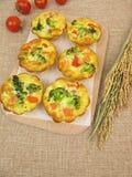 Muffin Frittatas mit Reis, Karotten, Brokkoli und Tomaten lizenzfreies stockbild