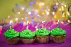 Muffin with green buttercream, pink background, candle. Birthday Royalty Free Stock Images