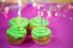 Muffin with green buttercream, pink background, candle. Birthday Royalty Free Stock Photography
