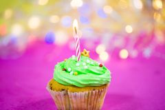 Muffin with green buttercream, pink background, candle. Birthday Stock Photography