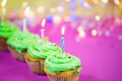 Muffin with green buttercream, pink background, candle. Birthday Royalty Free Stock Photo