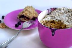 Muffin i en kopp av blåbär Arkivbilder