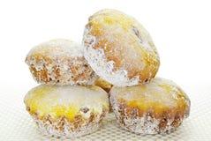 Muffin i pudrat socker på bordduk på en vit bakgrund Arkivbild