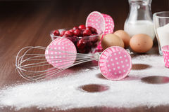 Muffin ingredients: the frozen cherry in a plate, eggs, flour on Stock Images