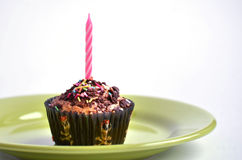 Muffin for kids party with pink candle at the top Stock Images