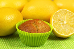 Muffin with lemons. Lemon mufin in green cupcake with whole yellow lemons Royalty Free Stock Images