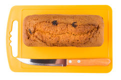 Muffin loaf with raisin and knife on orange cutting board. Isolated on white background. Top view Royalty Free Stock Images