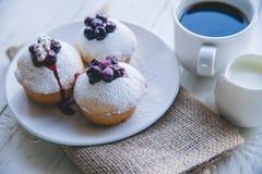 Muffin med bär på vit träbakgrund Arkivbilder