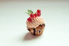 Muffin med den kräm- och röda vinbäret Kakor med kräm- och vit cu Fotografering för Bildbyråer