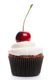 Muffin med det piskade kräm och Cherryet Royaltyfria Bilder