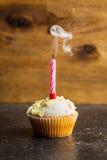 Muffin med en blåst stearinljus Arkivfoton