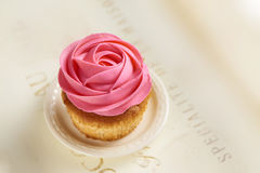 Muffin med en rosa färgrosgarnering Arkivbild