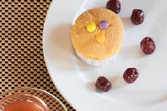 Muffin med godisen och krusbäret på vitt platta- och jordgubbete på tabellen royaltyfria foton