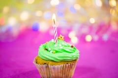 Muffin med grön buttercream, rosa bakgrund, stearinljus Arkivbild