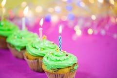 Muffin med grön buttercream, rosa bakgrund, stearinljus Royaltyfri Foto