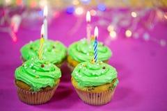 Muffin med grön buttercream, rosa bakgrund, stearinljus Royaltyfri Fotografi