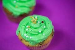 Muffin med grön buttercream, rosa bakgrund, stearinljus Royaltyfria Bilder