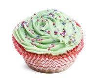Muffin med grön isläggning och strössel mot vitbakgrund Royaltyfria Foton