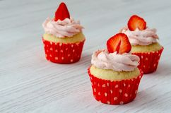 Muffin med jordgubbegarnering på en vit träbakgrund royaltyfri fotografi