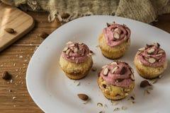 Muffin med jordgubbeskum och mandlar på den lantliga trätabellen Arkivbild