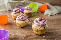 Muffin med jordgubbeskum och mandlar på den lantliga trätabellen Royaltyfri Bild