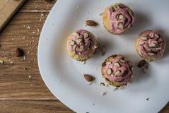 Muffin med jordgubbeskum och mandlar på den lantliga trätabellen Royaltyfria Bilder