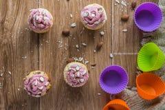 Muffin med jordgubbeskum och mandlar på den lantliga trätabellen Royaltyfri Fotografi