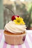 Muffin med körsbär och blomman Arkivfoto