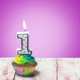 Muffin med nummer ett på en purpurfärgad bakgrund Royaltyfri Foto