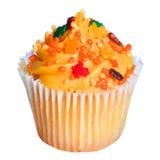 Muffin med orange glasyr på kaka och färgade stänk som isoleras på vit. Söt mat för allhelgonaafton Arkivbild
