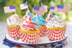 Muffin med röd-vit-och-blått glasyr på kaka och amerikanska flaggan royaltyfria foton