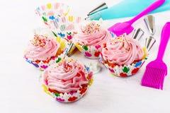 Muffin med rosa färger piskad kräm- virvel och konfekt spolar ren Arkivbilder