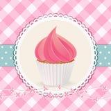 Muffin med rosa isläggning på rosa ginghambakgrund Arkivfoton