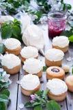 Muffin med smör lagar mat med grädde och fjädrar vita blommor Royaltyfria Bilder